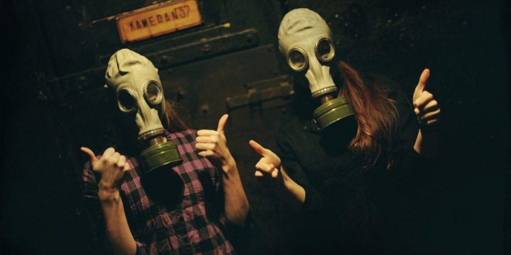 two girls wearing has masks inside escape room