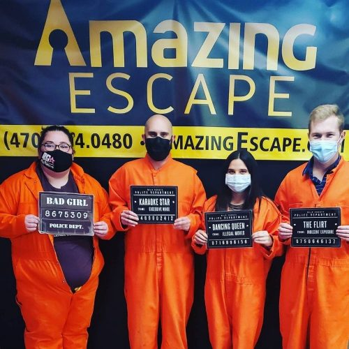 group of four people dressed as prisoners that just played the prison break escape game