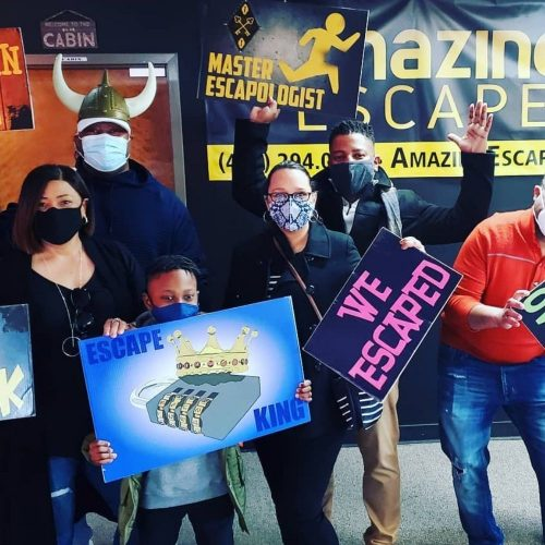guys holding signs that they've escaped on of the challenges at Amazing Escape