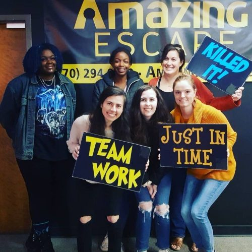 group of women that escaped the room with team work sign in their hands