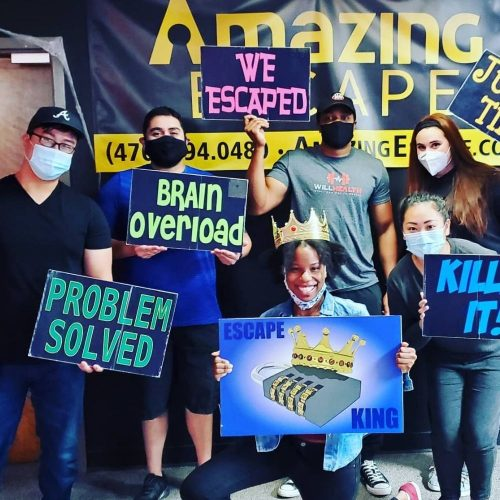 guys holding signs that say they've escaped the room